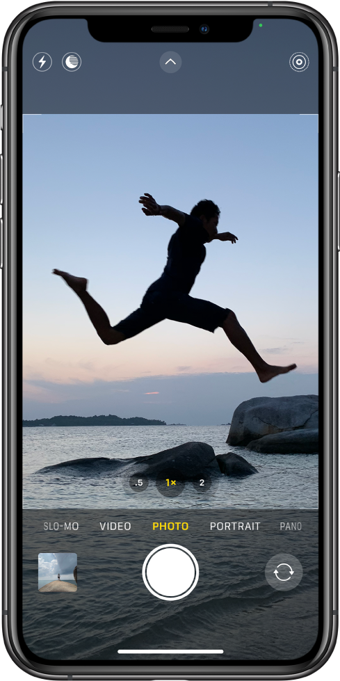 The Camera screen in Photo mode, with other modes to the left and right below the view finder. The buttons for Flash, Night mode, Camera Controls, and Live Photo are at the top of the screen. Below the camera modes are, from left to right, the Photo and Video Viewer button, the Take Picture button, and the Camera Chooser Back Facing button.