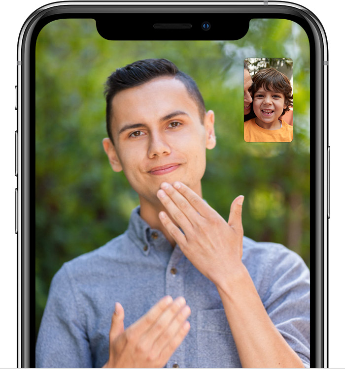 An iPhone screen showing a man signing in a FaceTime video call.