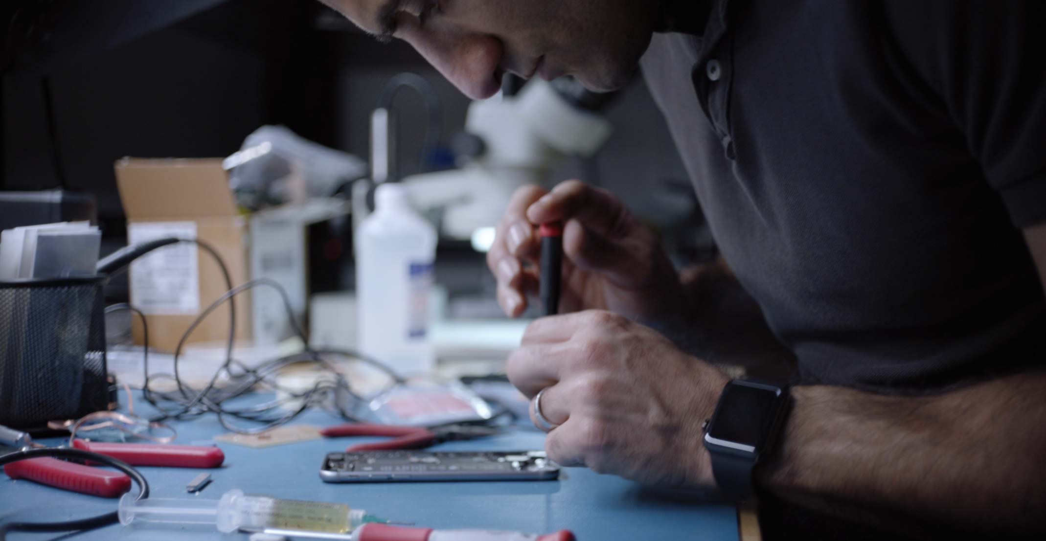 Ehsan, an engineering manager for Apple's Sensing Product Design group, works on an iPhone in an engineering lab.