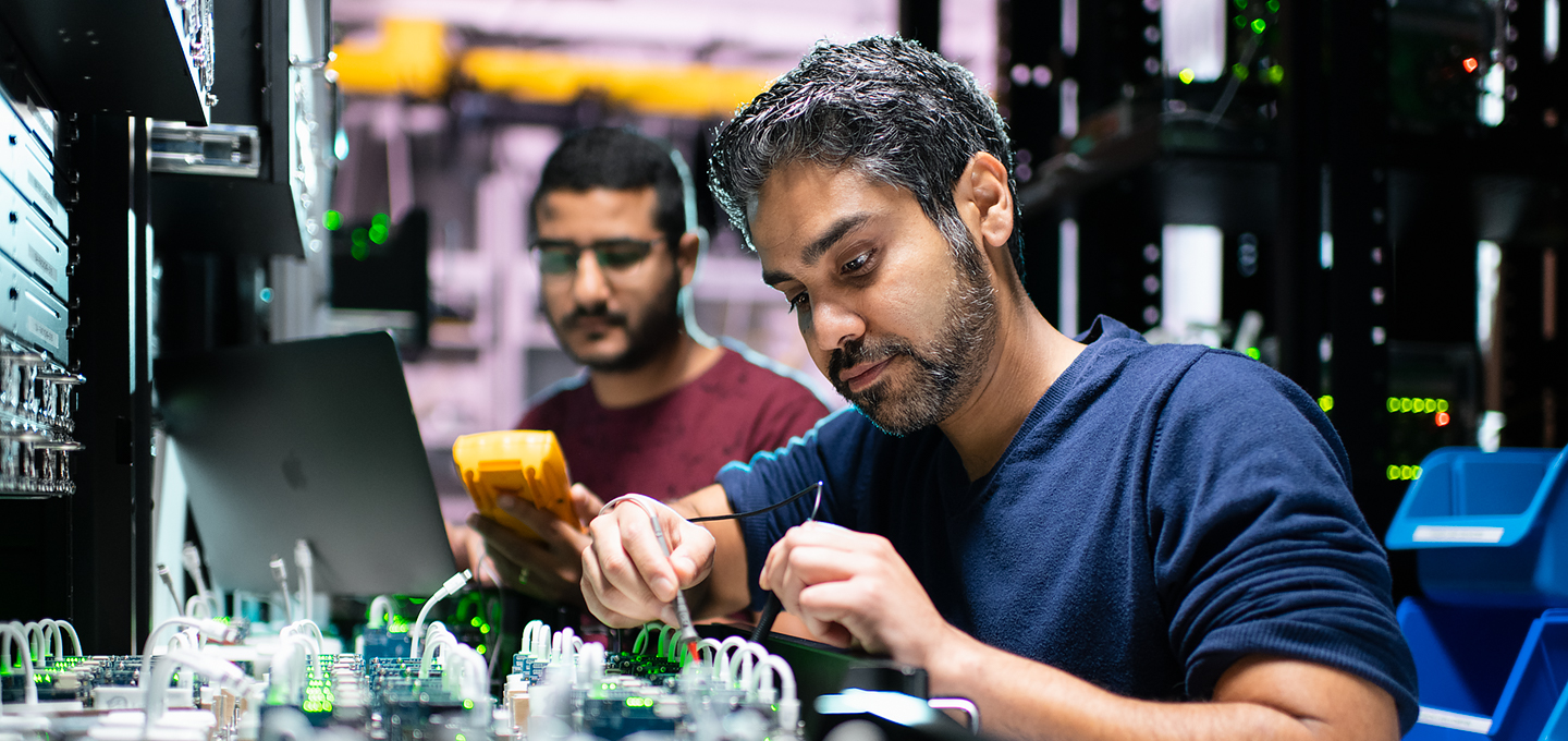 Two Apple engineers work on iPhone components in a lab