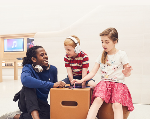 An Apple retail employee demonstrates an iPad to children.