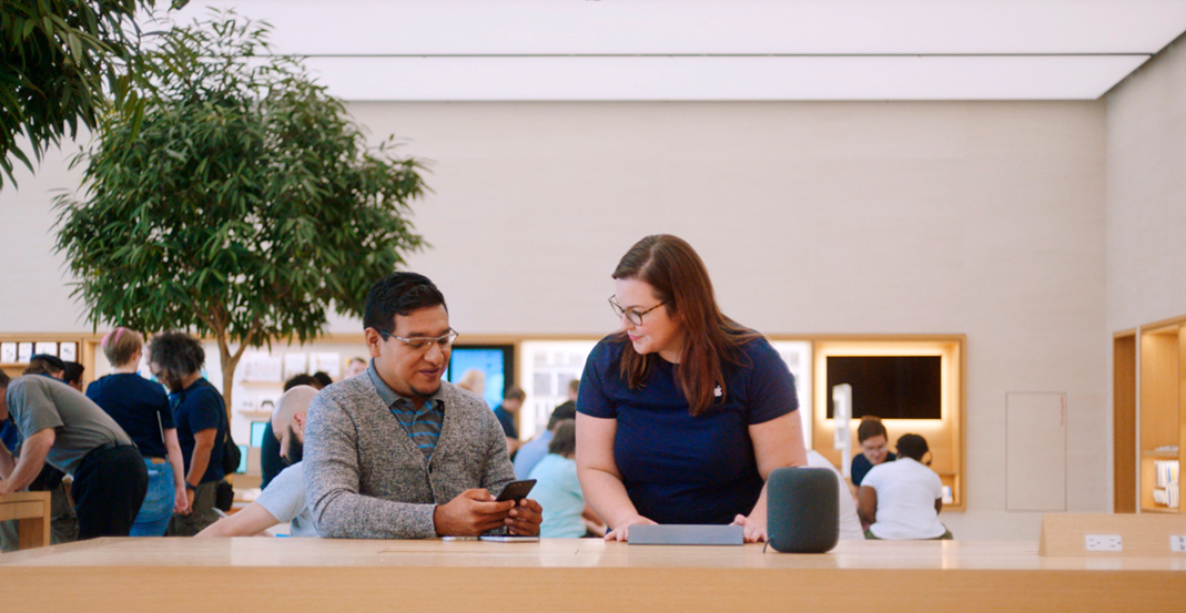 Melissa, an Apple Store Genius, helps a customer resolve an issue with his iPhone.