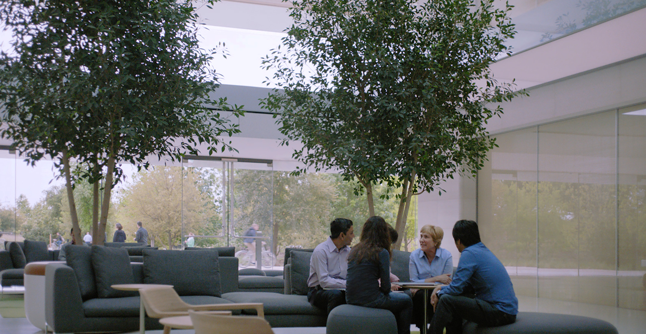 Giulia, who leads a natural language processing team, sits at a table along with other Apple employees.