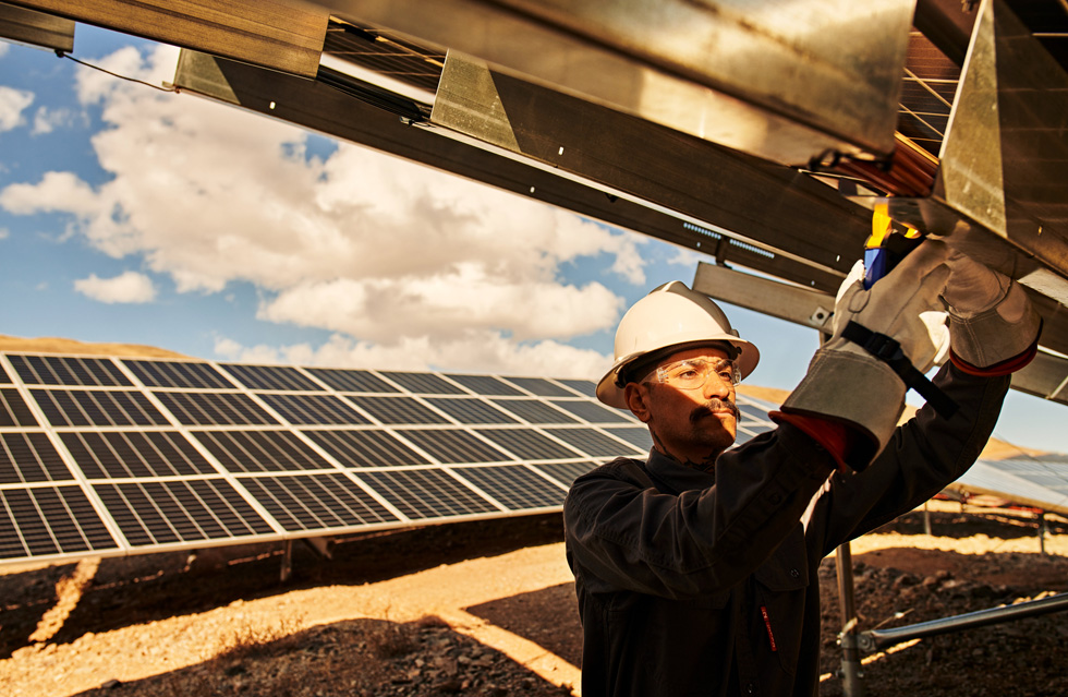 A technician works on a solar panel outdoors.