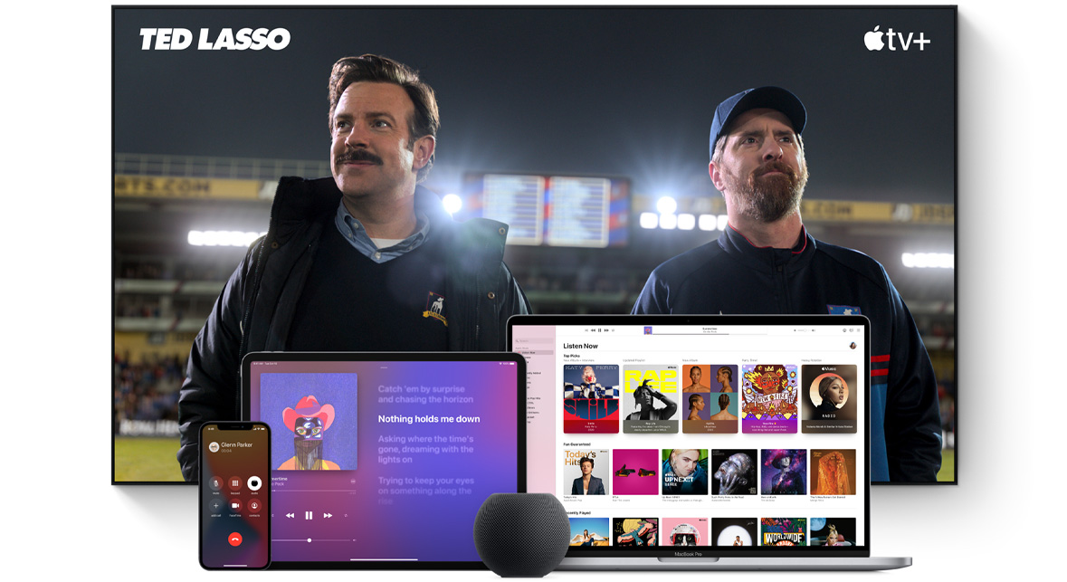 Large TV screen showing two coaches on a football field. A MacBook Pro, an iPad, an iPhone, and a Space Gray HomePod mini are arranged in front.