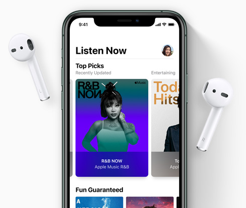 iPhone with AirPods on either side, music artwork on screen.